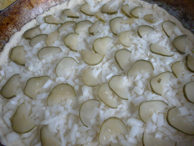 Вторым слоем на пиццу выкладываем соленые огурцы